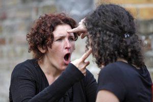 twee improvisatietheaterspelers die elkaar aanraken en waarvan de ene een verontwaardigde en verbaasde gezichtsuitdrukking heeft