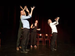 Three improvisers looking up, arms in the air